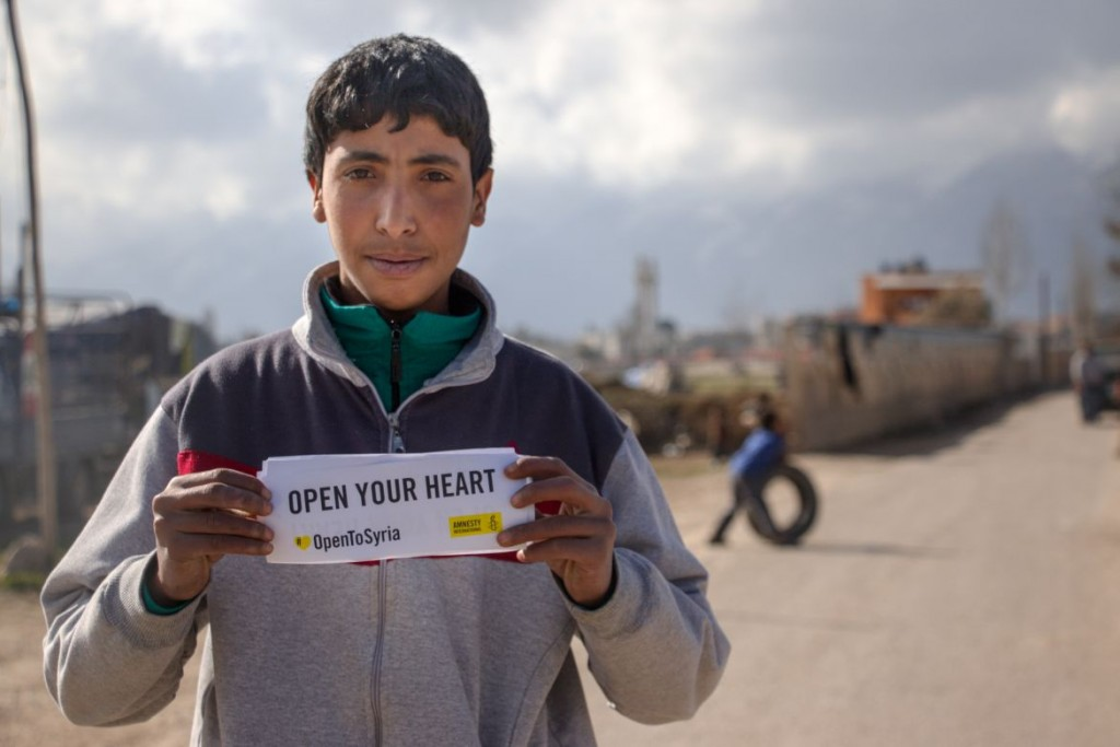 """Syrian refugees in a refugee camp in the Bekaa Valley in Lebanon holding posters saying """"Open Your Eyes"""" """"Open Your Arms"""" """"Open your hearts"""". Photographs supporting the Syria refugee campaign"""